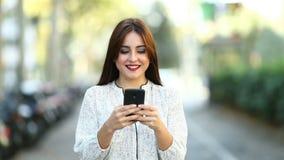Mujer que camina y que usa el teléfono en la cámara lenta de la calle