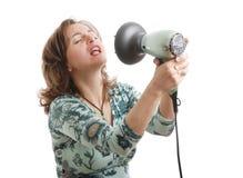 Mujer que canta con el hairdryer Foto de archivo libre de regalías