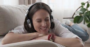 Mujer que canta mientras que escucha la música en los auriculares almacen de metraje de vídeo
