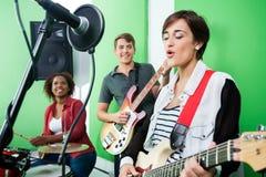 Mujer que canta mientras que banda que juega Musical imagen de archivo