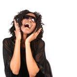 Mujer que canta mientras que escucha la música en Headphon Foto de archivo