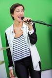 Mujer que canta mientras que sostiene el micrófono adentro fotos de archivo