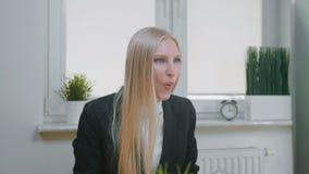 Mujer que celebra éxito en oficina Sentada femenina rubia elegante en el lugar de trabajo que se sostiene en el paquete de las ma almacen de video
