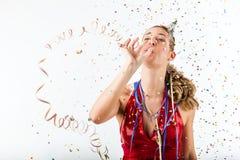 Mujer que celebra cumpleaños con el sombrero del bobinador de cintas en modo continuo y del partido Imagen de archivo