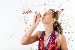 Mujer que celebra cumpleaños con el sombrero del bobinador de cintas en modo continuo y del partido Fotografía de archivo libre de regalías