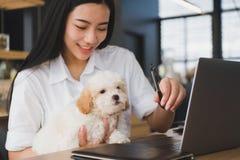 Mujer que celebra el perro adorable en el restaurante del café adolescente femenino s Fotografía de archivo