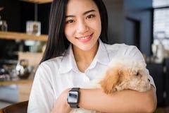 Mujer que celebra el perro adorable en el restaurante del café adolescente femenino w Imágenes de archivo libres de regalías