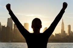 Mujer que celebra en la salida del sol en New York City fotos de archivo