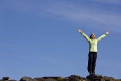 Mujer que celebra encima de una montaña Fotografía de archivo