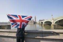 Mujer que celebra la bandera británica delante de la cara contra Big Ben en Londres, Inglaterra, Reino Unido Imagen de archivo libre de regalías