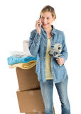 Mujer que celebra la cinta adhesiva mientras que usa el teléfono por las cajas apiladas foto de archivo libre de regalías
