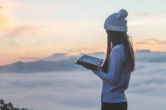 Mujer que celebra la lectura de la biblia en la montaña en la imagen de la mañana foto de archivo