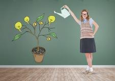 Mujer que celebra la regadera y el dibujo del dinero y gráficos de la idea en ramas de la planta en la pared Imagen de archivo libre de regalías