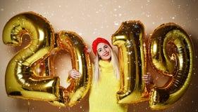 Mujer que celebra la risa feliz del partido de Navidad del Año Nuevo en blusa amarilla del suéter con los globos 2019 del oro fotos de archivo
