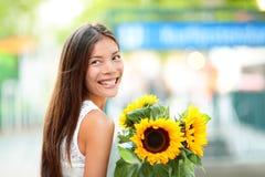 Mujer que celebra la sonrisa de la flor del girasol feliz Imagenes de archivo