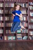 Mujer que celebra los libros y el salto Foto de archivo
