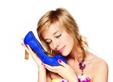 mujer que celebra un zapato azul en un almacén Fotos de archivo libres de regalías