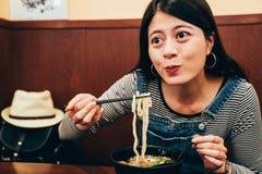 Mujer que cena con cocina japonesa sabrosa foto de archivo