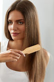 Mujer que cepilla el pelo largo sano hermoso con el retrato del cepillo Imagen de archivo