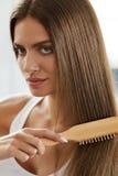 Mujer que cepilla el pelo largo sano hermoso con el retrato del cepillo Imágenes de archivo libres de regalías