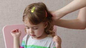 Mujer que cepilla su pelo de la hija en casa Familia feliz conceptual almacen de metraje de vídeo