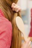 Mujer que cepilla su pelo largo en cuarto de baño Fotografía de archivo