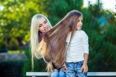Mujer que cepilla sus vaqueros del pelo de la hija al aire libre foto de archivo