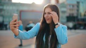 Mujer que charla en línea en smartphone de la tenencia de la ciudad almacen de video