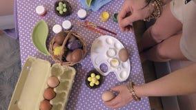 Mujer que clasifica los huevos de Pascua