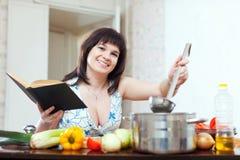 Mujer que cocina con el libro foto de archivo