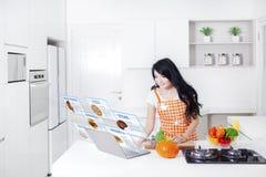 Mujer que cocina con el ordenador portátil y recetas virtuales Imágenes de archivo libres de regalías