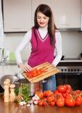 Mujer que cocina con los tomates en hogar Foto de archivo