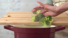 Mujer que cocina el bróculi en la cocina almacen de video