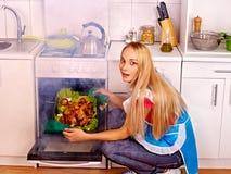Mujer que cocina el pollo en la cocina Fotos de archivo