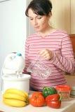 Mujer que cocina en la cocina Fotos de archivo libres de regalías