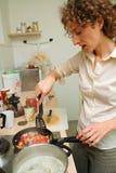 Mujer que cocina en la cocina Foto de archivo libre de regalías