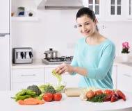 Mujer que cocina en la nueva cocina que hace el alimento sano con los vehículos Fotos de archivo libres de regalías