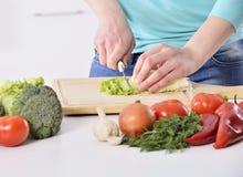 Mujer que cocina en la nueva cocina que hace el alimento sano con los vehículos