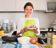 Mujer que cocina la carne con arroz Imágenes de archivo libres de regalías