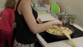 Mujer que cocina la comida de la fritada Higo con el espárrago, la pimienta, el maíz y la zanahoria metrajes