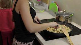 Mujer que cocina la comida de la fritada Higo con el espárrago, la pimienta, el maíz y la zanahoria almacen de video