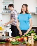 Mujer que cocina la comida mientras que platos que se lavan del hombre Fotografía de archivo