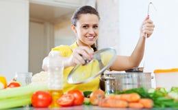 Mujer que cocina la comida vegetariana en cazo Fotografía de archivo libre de regalías