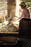 Mujer que cocina la goma del arroz para hacer los tallarines de arroz, Vietnam