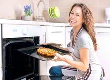 Mujer que cocina la pizza Imagen de archivo libre de regalías