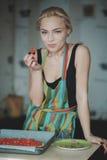 Mujer que cocina la pizza en la cocina Fotografía de archivo libre de regalías