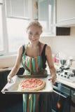 Mujer que cocina la pizza en la cocina Fotos de archivo libres de regalías