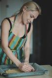 Mujer que cocina la pizza en la cocina Fotos de archivo