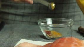 Mujer que cocina la preparación de color salmón de los pescados en casa - de las especias almacen de metraje de vídeo