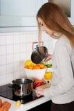 Mujer que cocina la sopa Fotos de archivo